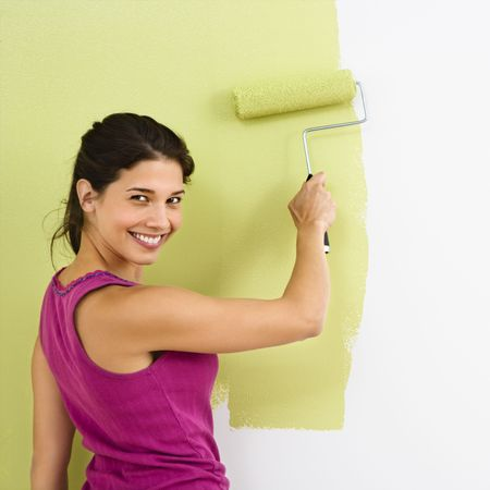domestic scenes: Pretty smiling woman painting interior wall of home with paint roller.
