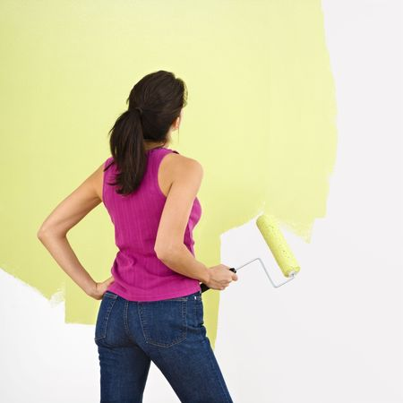 Woman standing and looking at partially painted wall holding paint roller. Stock Photo