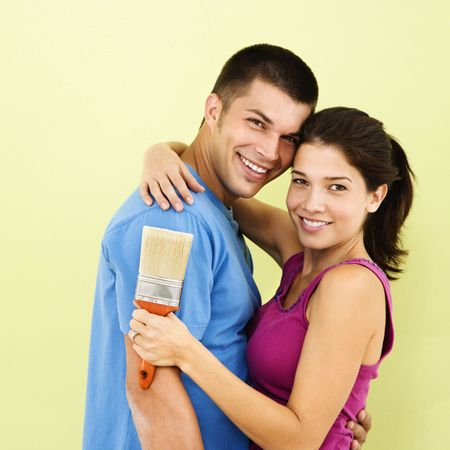 Happy smiling couple holding paintbrush in front of freshly painted interior wall. Stock Photo - 2061098