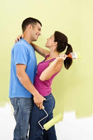 Couple hugging and smiling at eachother holding paintbrushes in front of partially painted wall.