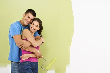 Attractive smiling couple posing in front of partially painted wall holding paint roller. photo