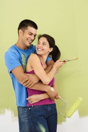 Couple smiling and embracing in front of partially painted interior wall holding paintbrush and roller. photo