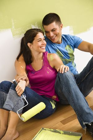 Couple sitting on floor smiling taking a break from painting home. photo