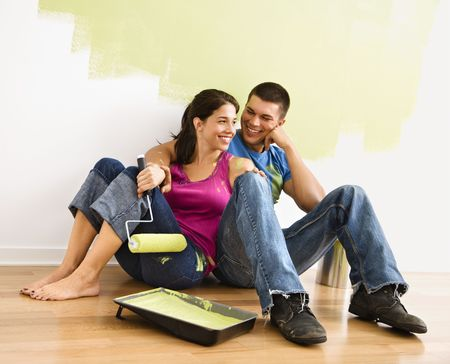 Couple sitting on floor smiling in front of partially painted wall in home. photo