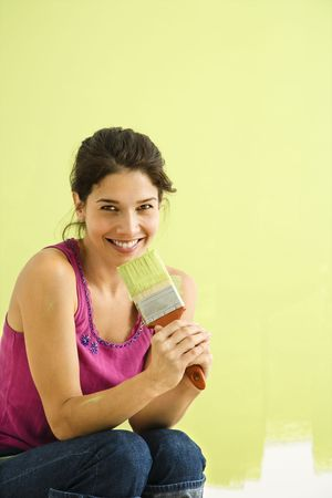 woman kneeling: Pretty smiling woman kneeling in front of partially painted wall holding paintbrush.