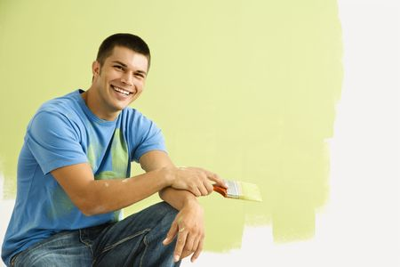 only mid adult men: Smiling man kneeling in front of partially painted wall holding paintbrush.