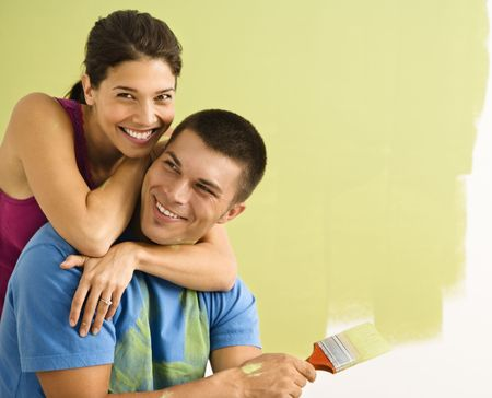 Happy smiling couple painting interior wall of home. photo