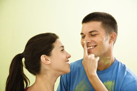 Playful smiling woman putting paint on man's nose. photo