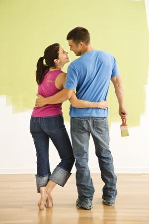 Attractive couple standing in front of partially painted wall with arms around eachother smiling. photo