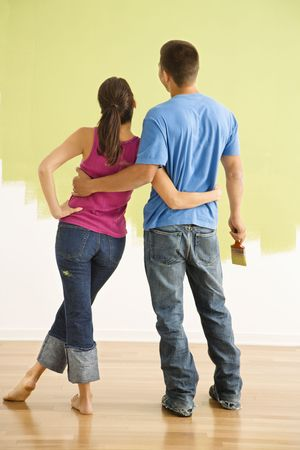 Attractive couple standing in front of partially painted wall with arms around eachother. Stock Photo