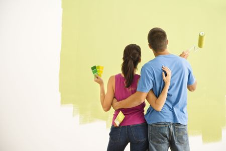 eachother: Attractive couple standing in front of partially painted wall with arms around eachother. Stock Photo