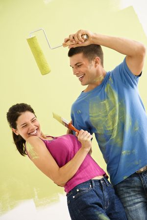 Attractive couple standing in front of partially painted wall playfully putting paint on eachother. photo