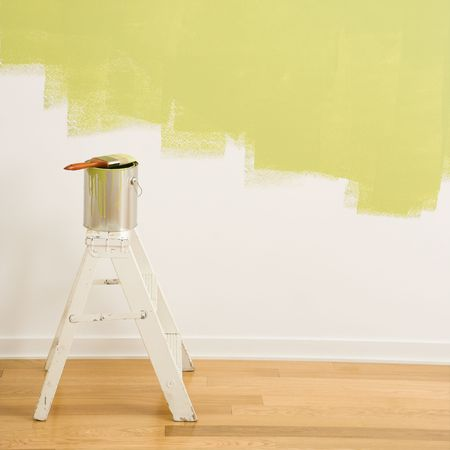 step ladder: Paintbrush on can on top of step ladder with painted wall.