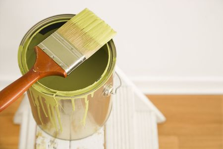 stepladder: High angle view of paintbrush resting on paint can on stepladder.