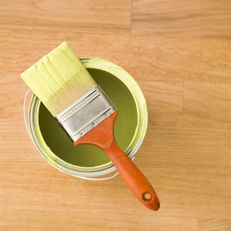 high angle: High angle view of paintbrush resting on paint can on wood floor.