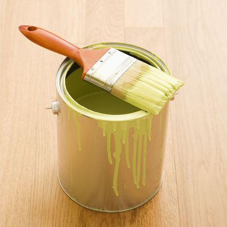 Paintbrush resting on paint can on wood floor. Stock Photo - 2043809