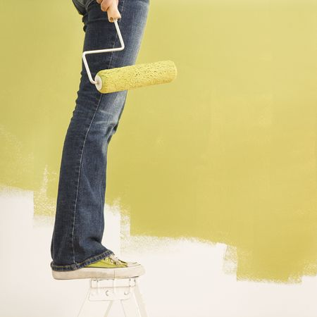 Legs of woman standing on stepladder holding paint roller with painted wall. photo