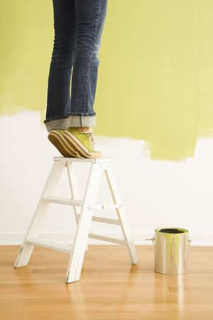 stepladder: Legs of woman standing on tiptoe on stepladder with paint can and painted wall.