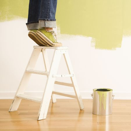 Legs of woman standing on tiptoe on stepladder with paint can and painted wall. Stock Photo - 2043761