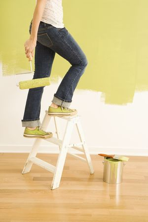 Legs of woman climbing stepladder holding paint roller. photo