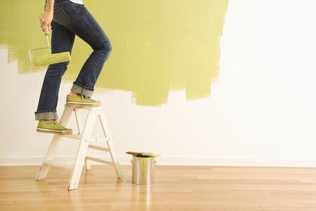 stepladder: Legs of woman climbing stepladder holding paint roller.
