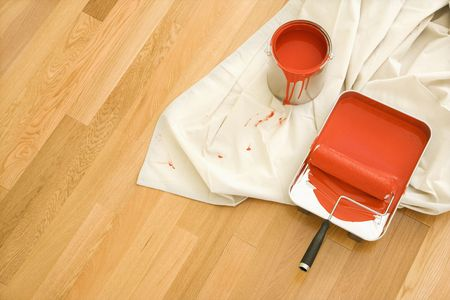 floor cloth: High angle view of painting supplies on drop cloth on wood floor.
