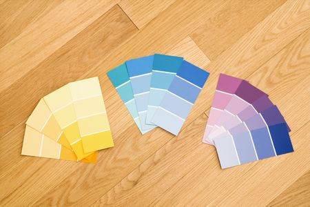 Paint color swatches grouped together by color on wood floor. Stock Photo - 2043465