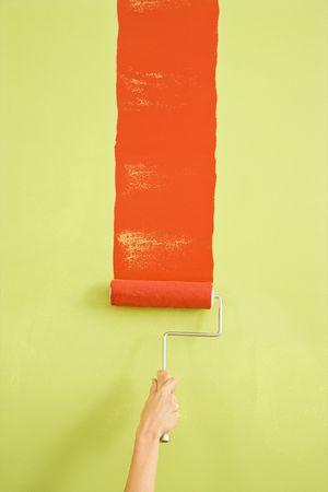 hand schilderen: Kaukasische vrouwelijke kant schilderij rode streep op de groene muur. Stockfoto