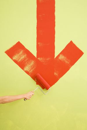 downwards: Caucasian female hand painting red downwards arrow on wall. Stock Photo