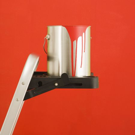 Still life of paint can on step ladder in front of red wall. photo