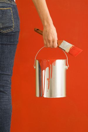 Caucasian female hand and leg holding paint can and paintbrush. photo