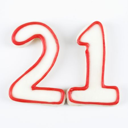 twenty one: Sugar cookies in the shape of the number twenty one outlined in red icing.