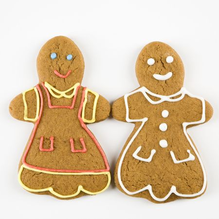 Two female gingerbread cookies holding hands. photo