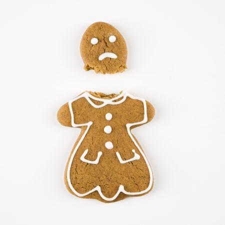 beheaded: Frowning female gingerbread cookie broken in half. Stock Photo
