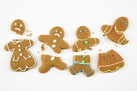 gingerbread man: Four frowning male and female gingerbread cookies broken into pieces.