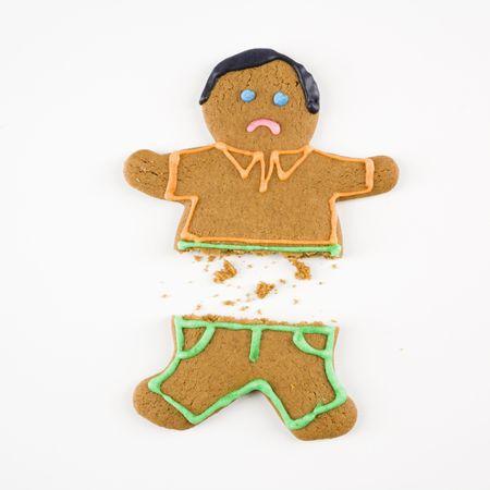 dysfunctional: Frowning male gingerbread cookie broken in half.