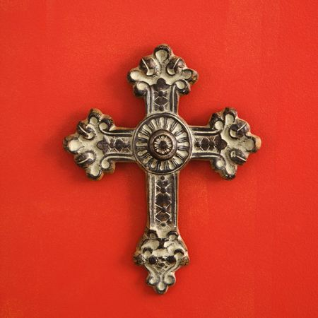 home accent: Ornate religious cross hanging on red wall.