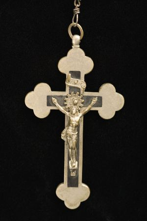 Close up of crucifix pendant against black background. Stock Photo