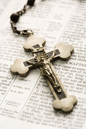 doctrine: Crucifix on rosary lying on open Bible.