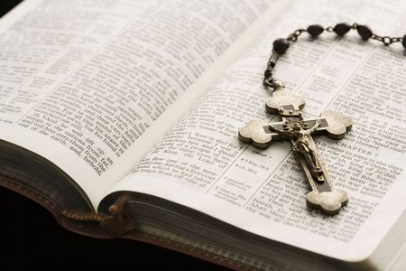 Rosary with crucifix lying on open Bible. Stock Photo