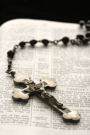 scripture: Rosary with crucifix lying on open Bible. Stock Photo