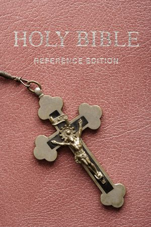 rosary: Crucifix lying on cover of closed Holy Bible.