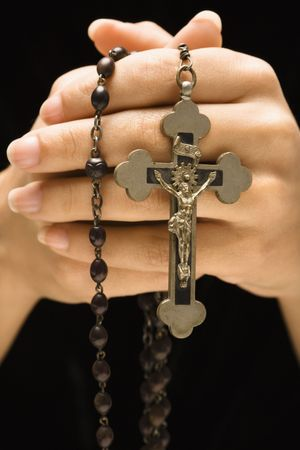 Woman holding rosary with crucifix.
