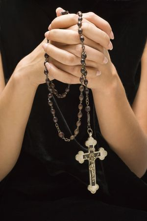 Woman holding rosary with hands clasped together.