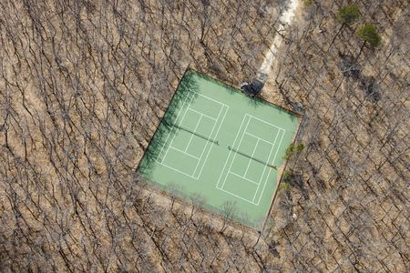 wooded: Aerial view of tennis court in bare wooded area. Stock Photo