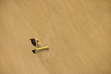 cropland: Aerial of farmer tilling crop field in farmland, USA.