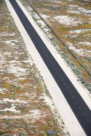 desolate: Aerial of two lane highway through desolate landscape. Stock Photo