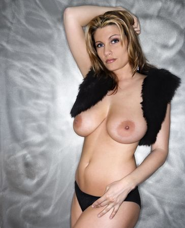 Topless Caucasian woman in fur vest and panties looking at viewer.