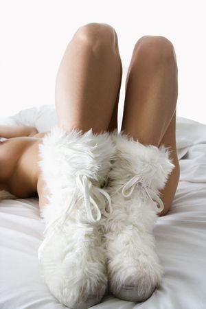 Caucasian woman lying on bed wearing furry boots.