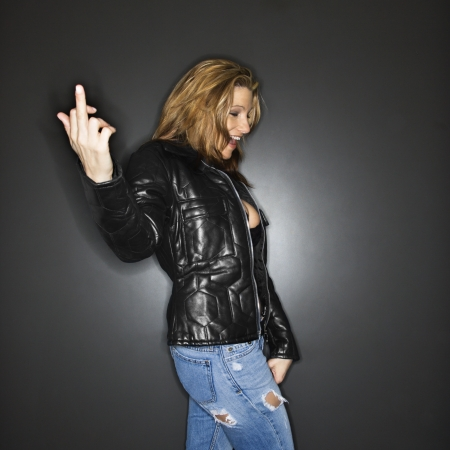 Caucasian woman making vulgar gesture to viewer. photo